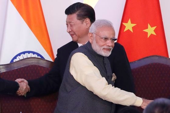2016年10月、インド・ゴアで開かれたBRICS首脳会談で、中国の習近平国家主席(左)とインドのナレンドラ・モディ首相(右)が握手を終えた後、それぞれの位置に移動している。最近、カシミール中印国境地帯で両国軍隊の衝突によって数十人の死亡者が発生し、両国の間では葛藤が深まっている。[中央フォト]
