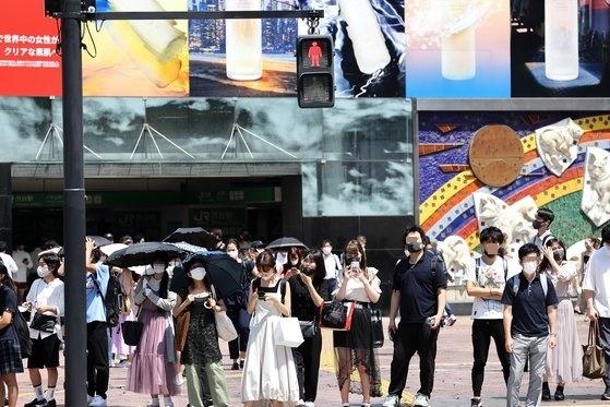 昼間の体感温度が41度まで上がるなど猛暑が続いた19日午後、市民が渋谷駅近くの横断歩道を渡っている。チャン・ジンヨン記者