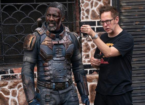 """DC漫画原作のアンチヒーロー映画『ザ・スーサイド・スクワッド """"極""""悪党、集結』の演出を手がけたジェームズ・ガン監督(右)がロケ地で主演俳優イドリス・エルバと話しを交わしている姿だ。[写真 ワーナーブラザース・コリア]"""
