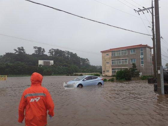 17日午前7時9分、済州市朝天邑の道路が冠水して車両が孤立し、消防隊員が救助している。 写真=済州道消防安全本部
