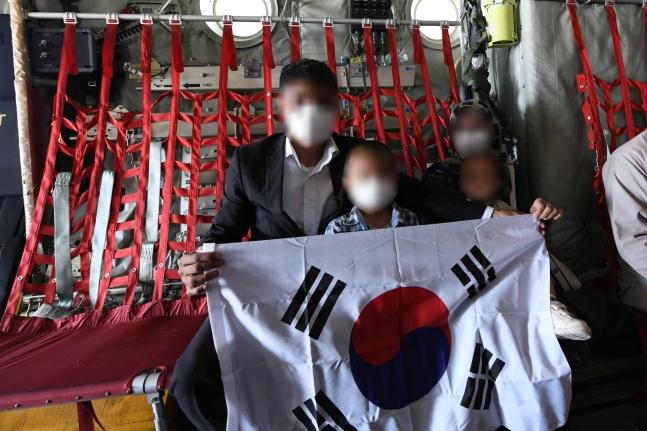 先月25日にアフガニスタンのカブール空港から韓国空軍のC130J輸送機に搭乗したアフガン協力者の家族が太極旗を広げて見せている。[写真 韓国空軍]