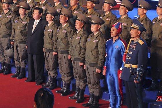 北朝鮮の金正恩(キム・ジョンウン)国務委員長が11日、国防発展展覧会開幕式でエアショーを行ったパイロットとともに記念写真を撮影している。前列右側から2番目に立っている人物は青色の独特の服装をしている。[写真 朝鮮中央通信=聯合ニュース]
